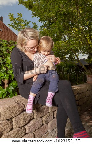 happy  mother and daughter in the garden having fun with mother tickle childs belly