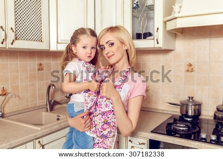 Happy mother and daughter in the kitchen aprons - stock photo