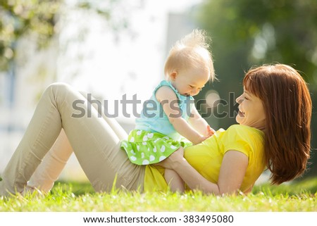 Happy mother and daughter in the park - stock photo
