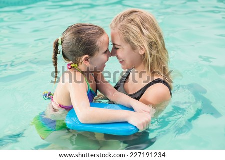 Happy mother and daughter in the swimming pool at the leisure center - stock photo