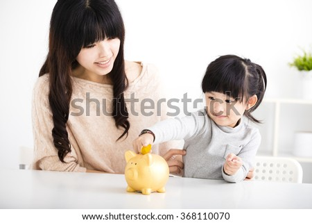 Happy mother and daughter Inserting Coin In Piggy bank   - stock photo