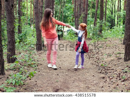 Happy mother and daughter looking at each other holding hands while walking on a forest path