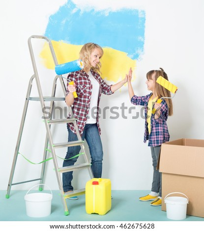 Happy mother and daughter makes repairs at home - painting big Ukrainian flag on wall at room.
