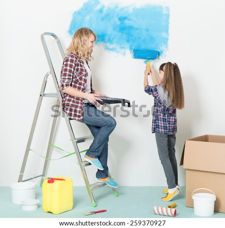 Happy mother and daughter makes repairs at home. Smiling girl painting wall at room.