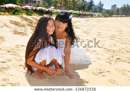 Happy mother and daughter on a beach - stock photo