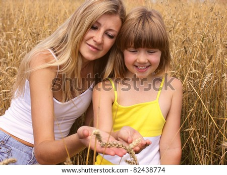 Happy mother and daughter on a field of wheat
