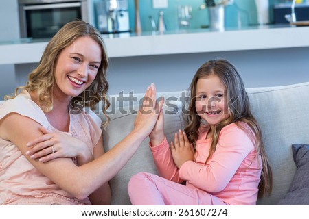Happy mother and daughter on the couch at home in the living room - stock photo