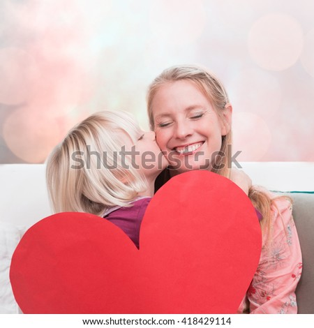 Happy mother and daughter on the couch with heart card against sun is up - stock photo