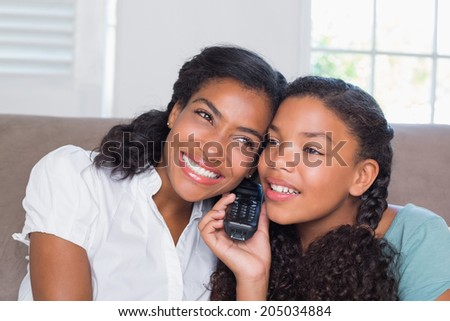 Happy mother and daughter on the phone together on sofa at home in living room - stock photo