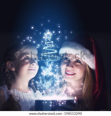 Happy mother and daughter opening Christmas gift - stock photo