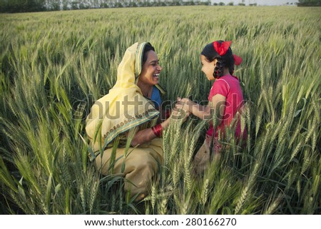 Happy mother and daughter playing in the field - stock photo