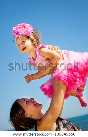 Happy mother and daughter playing on sky background - stock photo