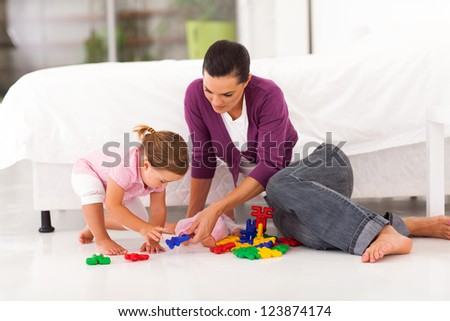 happy mother and daughter playing with toy on bedroom floor - stock photo