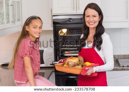 Happy mother and daughter posing with roast turkey at home in the kitchen - stock photo