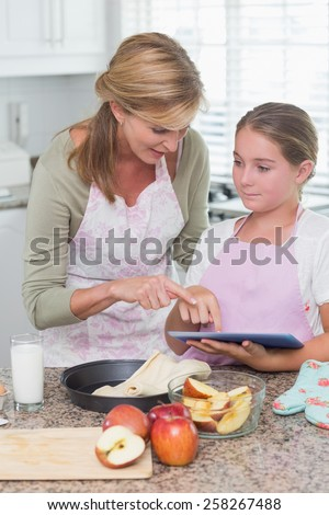 Happy mother and daughter preparing cake together at home in the kitchen - stock photo