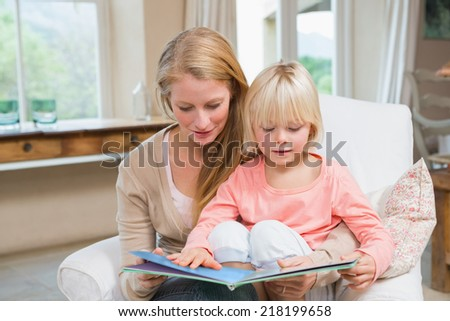 Happy mother and daughter reading together at home in the living room - stock photo