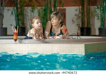 Happy mother and daughter relaxing by the pool with glass of coctail