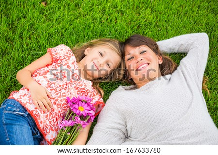 Happy mother and daughter relaxing outside on green grass. Spending quality time together, Real emotions - stock photo