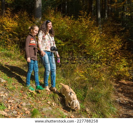 Happy mother and daughter resting in the autumn forest - stock photo
