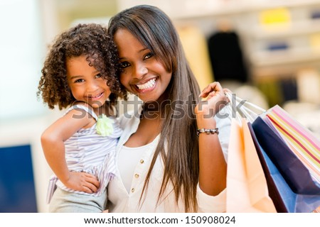 Happy mother and daughter shopping at a retail store  - stock photo