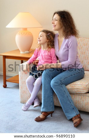 Happy mother and daughter sit on couch in cozy room; girl laughs