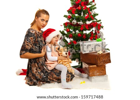Happy mother and daughter sitting down near Christmas tree with presents - stock photo