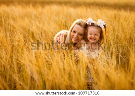 happy mother and daughter sitting in a wheat field. outdoor shot - stock photo