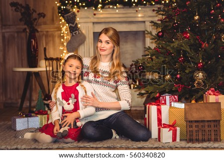 Happy mother and daughter sitting on floor with gift boxes and smiling at camera