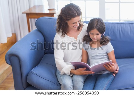 Happy mother and daughter sitting on the couch and reading book in the living room - stock photo