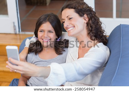 Happy mother and daughter sitting on the couch and taking selfie in the living room