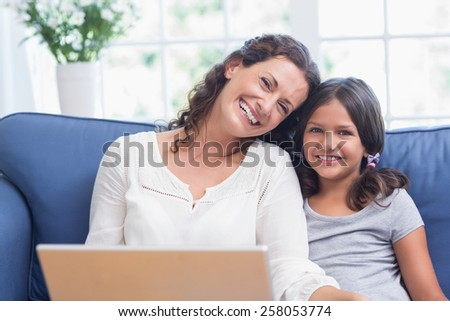 Happy mother and daughter sitting on the couch and using laptop in the living room - stock photo