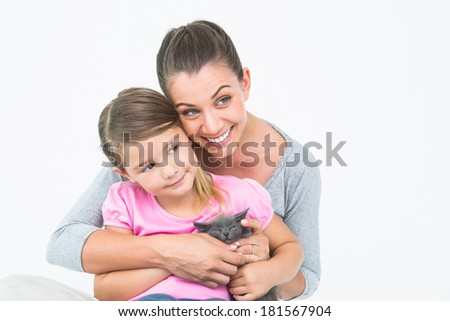 Happy mother and daughter sitting with pet kitten together on white background