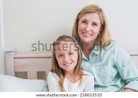 Happy mother and daughter smiling at camera in the bedroom - stock photo