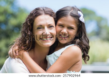 Happy mother and daughter smiling at camera in the garden