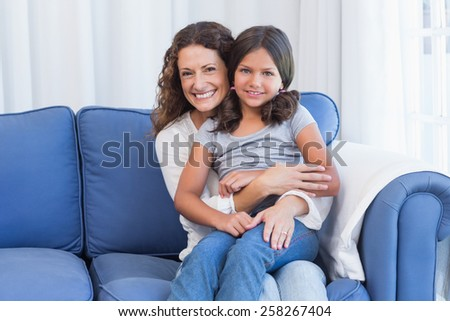 Happy mother and daughter smiling at camera in the living room - stock photo
