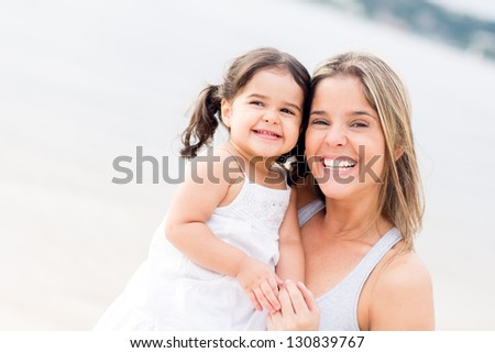 Happy mother and daughter smiling at the beach