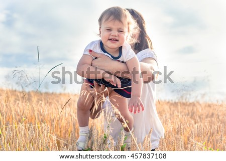 happy mother and daughter smiling outdoors in a field at sunset in summer - stock photo