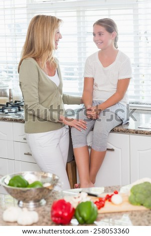 Happy mother and daughter talking together at home in the kitchen - stock photo