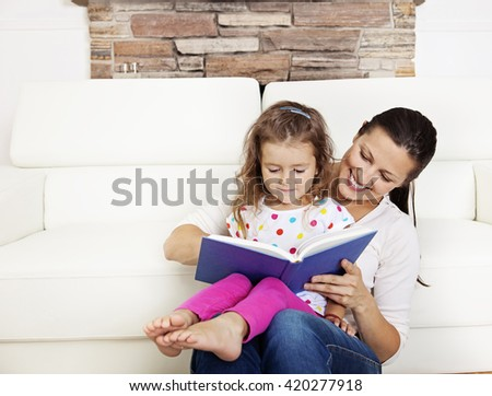 Happy mother and daughter together on the white couch, in living room, reading - stock photo