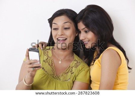 Happy mother and daughter using cell phone - stock photo