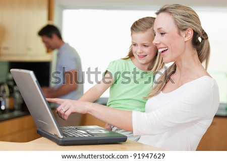 Happy mother and daughter using laptop together with father in the background