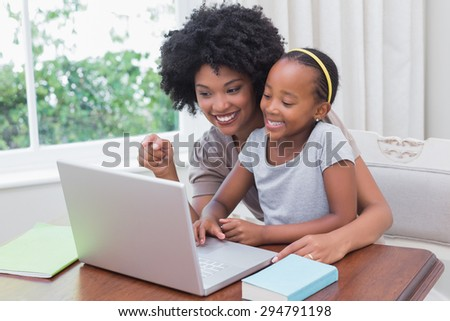 Happy mother and daughter using the laptop at home - stock photo