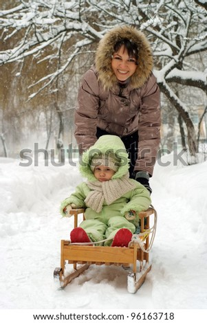 Happy mother and daughter walking on the street - stock photo
