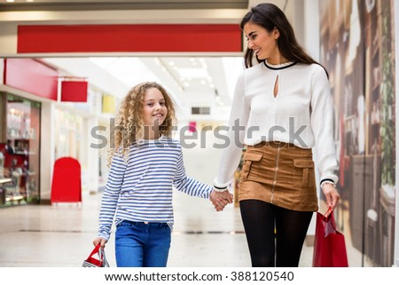 Happy mother and daughter walking with shopping bags in mall - stock photo