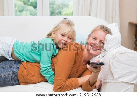 Happy mother and daughter watching tv at home in the living room