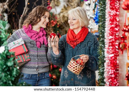 Happy mother and daughter with bauble basket and presents standing in Christmas store