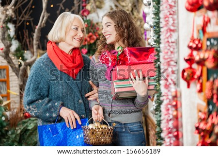 Happy mother and daughter with Christmas presents standing at store