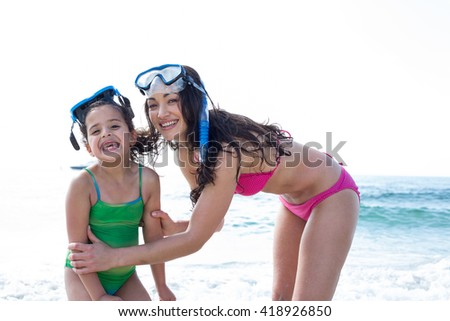 Happy mother and daughter with diving goggles at beach - stock photo