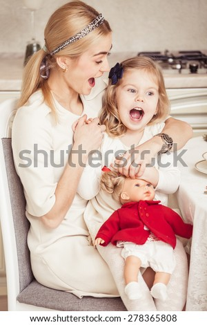 Happy mother and daughter with doll - stock photo