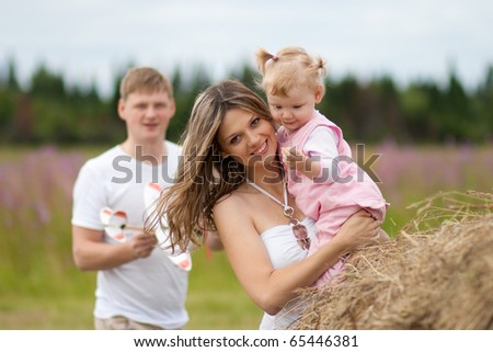 Happy mother and daughter with father in a background - stock photo